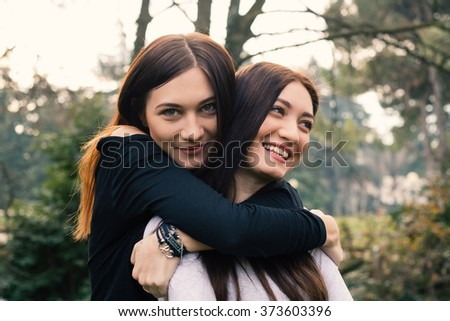 Smiling portrait of young sisters hugging outdoors in a park. - stock photo