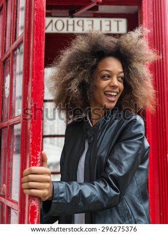 Smiling portrait of young woman close to red telephone box in London. - stock photo