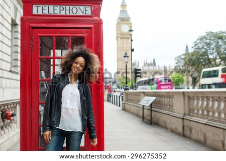 Smiling portrait of young woman close to red telephone box in London. Big Ben in the background. - stock photo