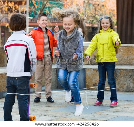 Smiling positive girl jumping while jump rope game with friends outdoor - stock photo
