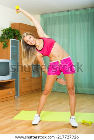 Smiling Positive Girl Working Out On Exercise Mat In The Living Room