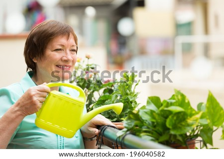 Smiling positive senior woman watering decorative flowers on balcony - stock photo
