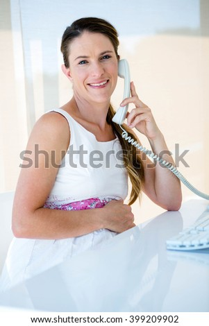 smiling pregnant businesswoman, in her office, on the phone - stock photo