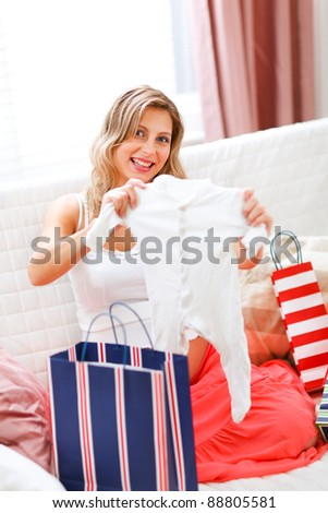 Smiling pregnant sitting on couch with shopping bags and examine baby sleeper