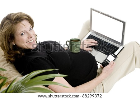 smiling pregnant woman in her 40's, with laptop, and phone, casual clothing, coffe cup on belly, blank screens - stock photo
