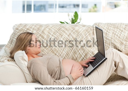 Smiling pregnant woman using her laptop lying on the sofa at home - stock photo