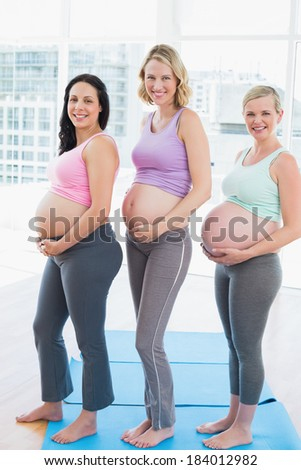 Smiling pregnant women standing in a row in a fitness studio