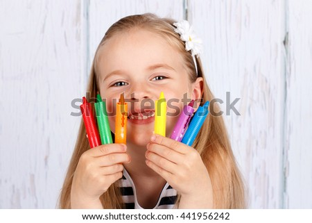 Smiling preschool girl holding crayons - stock photo
