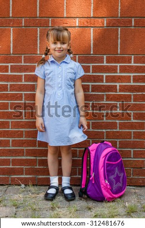 Smiling preschool girl in blue school uniform gingham dress and in mary jane shoes with backpack standing near the brick school wall.  Back to school.  - stock photo