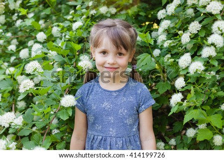 Smiling preschool girl in the park on spring green blossom bushes background. - stock photo