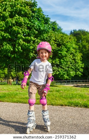 Smiling preschool girl with pink protective helmet on, roller skating  - stock photo
