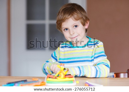 Smiling preschool kid boy having fun with dough, colorful modeling compound, sitting at table at home or nursery. Creative leisure with kids. - stock photo