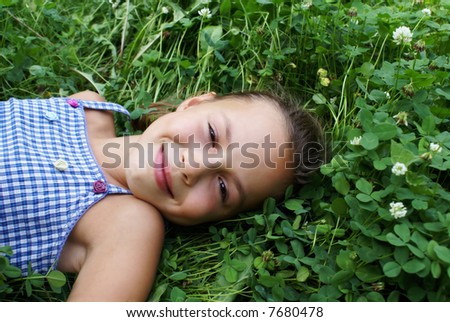 Smiling preteen girl on clover background - stock photo