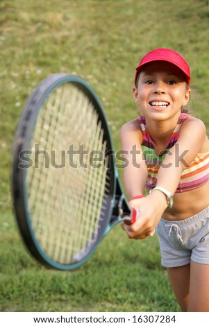 Smiling preteen girl playing tennis - stock photo