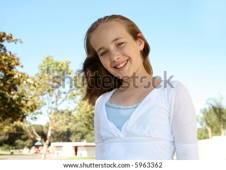 Smiling preteen pretty girl at the park - stock photo