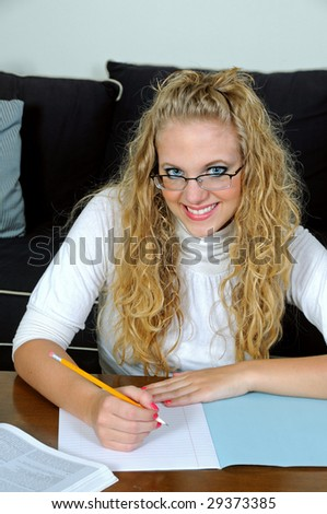 smiling, pretty blonde writing in exam book