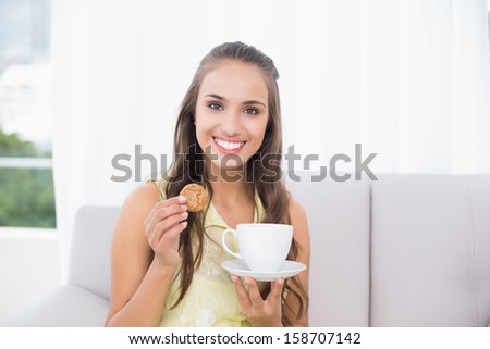 Smiling pretty brunette holding a cookie in bright living room