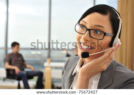 Smiling pretty business woman with headset in an office environment at foreground - stock photo