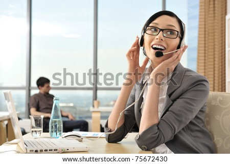 Smiling pretty business woman with headset in an office environment at foreground. Copyspace - stock photo