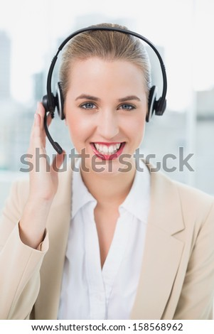 Smiling pretty call center agent in bright office wearing headset