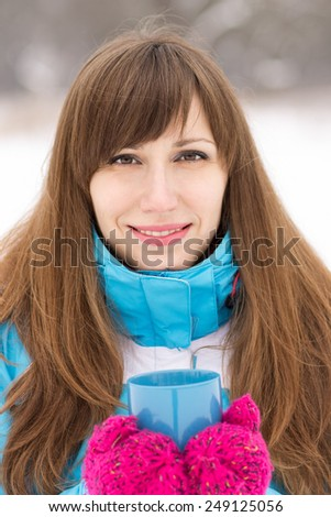 Smiling pretty girl holding cup of hot tea at winter outdoor. Young woman with long brown hair looking straight into camera - stock photo