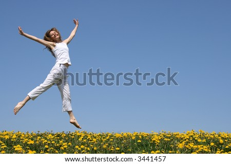 Smiling pretty girl in summer white clothes dancing in a flowering meadow. - stock photo