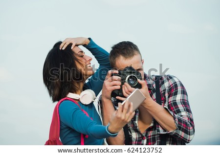 Smiling pretty girl or beautiful woman taking selfie on smartphone how handsome man, photographer, photographing with camera. Happy, young couple using technology. Summer vacation and travelling