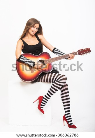 Smiling pretty girl playing the acoustic guitar  - stock photo