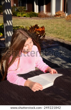 Smiling pretty girl reading a book outdoors. - stock photo