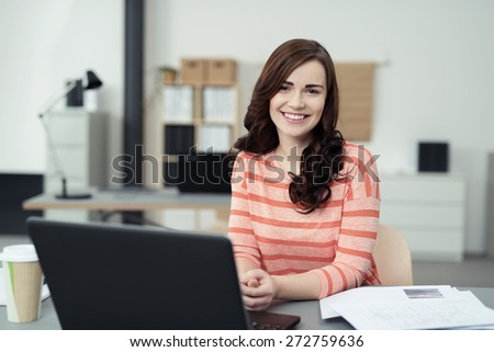 Smiling Pretty Girl Sitting at her Desk with Laptop Computer and Report Papers and Looking at the Camera. - stock photo