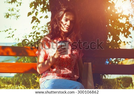 smiling pretty girl sitting on bench with morning coffee