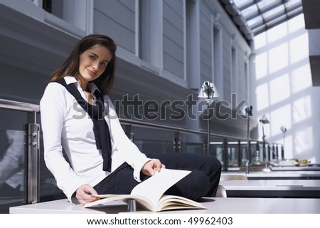 Smiling pretty girl sitting on desk in modern university library studying a book. - stock photo