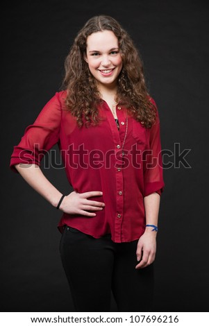 Smiling pretty girl with long brown curly hair. Fashion studio portrait isolated against black background. Wearing red shirt. - stock photo