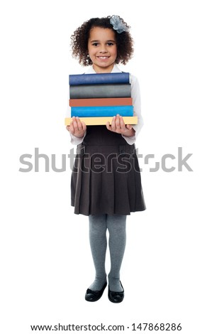 Smiling pretty kid holding pile of books - stock photo