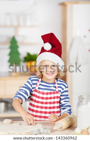 Smiling pretty little blond girl baking cookies during Advent standing at a kitchen counter in a red striped apron and Santa hat - stock photo