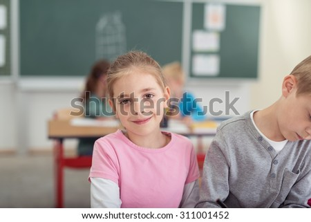 Smiling pretty little girl in the school room sitting alongside a young boy sharing a desk with other students visible behind - stock photo