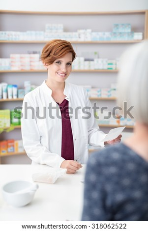 Smiling pretty pharmacist in a drugstore holding a prescription fro medicine brought in by an elderly lady, stocked shelves in the background