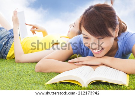 smiling pretty students lying on the grassland with books - stock photo