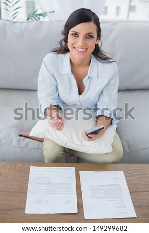 Smiling pretty woman doing her accounts in her living room - stock photo