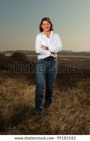 Smiling pretty woman middle aged enjoying outdoors. Feeling free standing in grassy dune landscape. Clear sunny spring day with blue sky. - stock photo