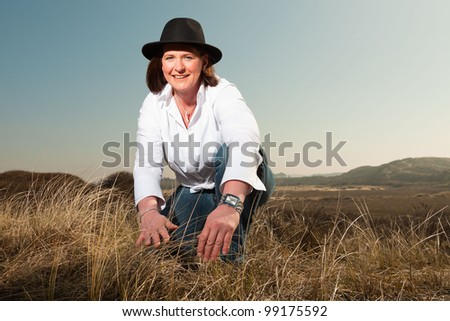 Smiling pretty woman middle aged with a hat enjoying outdoors. Touching grass of dunes. Clear sunny spring day with blue sky. - stock photo