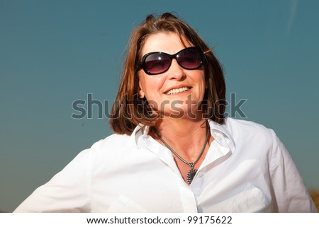 Smiling pretty woman middle aged with sunglasses enjoying outdoors. Feeling free. Clear sunny spring day with blue sky. - stock photo