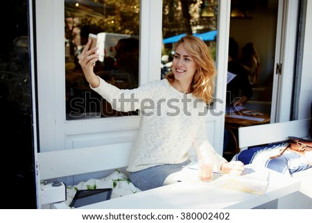 Smiling pretty woman photographing herself with mobile phone camera during breakfast in sidewalk cafe, young cheerful female making photo with cell telephone while waiting for her order in coffee shop - stock photo
