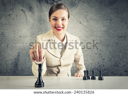 Smiling pretty woman sitting and playing chess - stock photo