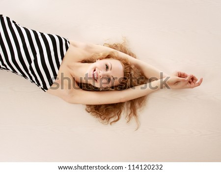 Smiling pretty woman stretching on the floor - stock photo