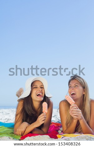 Smiling pretty women lying on their towel eating ice cream having holidays together - stock photo