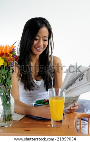 Smiling pretty young Asian woman reading newspaper- breakfast in bed