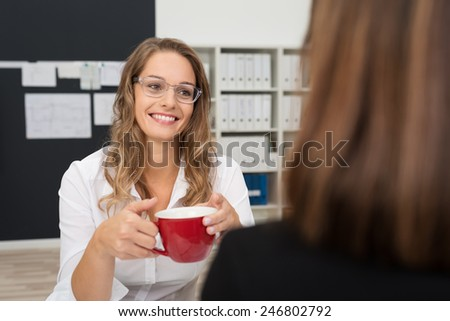 Smiling Pretty Young Office Woman Talking to her Female Office-mate While Having a Cup of Coffee During Break Time. - stock photo