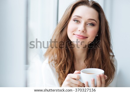 Smiling pretty young woman drinking coffee near the window - stock photo