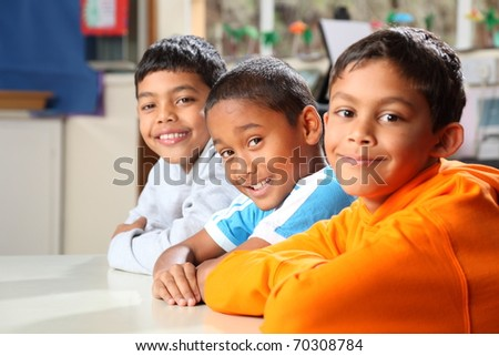 Smiling primary school friends together in class